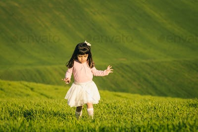 Little girl with pink shirt and skirt in a meadow. Disgusted face. She does not like the field