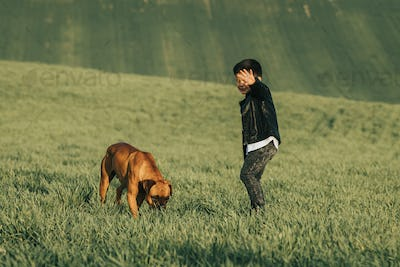 Little boy and dog in field. Boxer dog