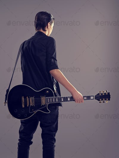 Guitarist with a  black electric guitar. Rear view