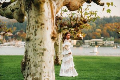 A bride in a white wedding dress with a belt in the Old town of Velden am werter see.A model in an