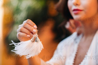 Earrings with white fringe in the hands of the bride at a wedding in Italy.wedding Earrings white