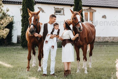 A family in white clothes with their son stand near two beautiful horses in nature. A stylish couple