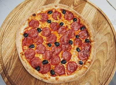 Top view. Picture of prepared delicious pizza with sausage rings and olives