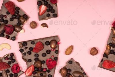 Top view of delicious chocolate with nuts and fruits isolated on pink