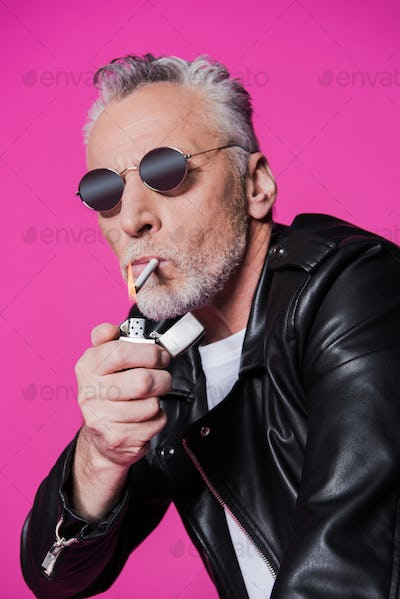 Stylish handsome senior man in sunglasses and leather jacket holding lighter and smoking cigarette