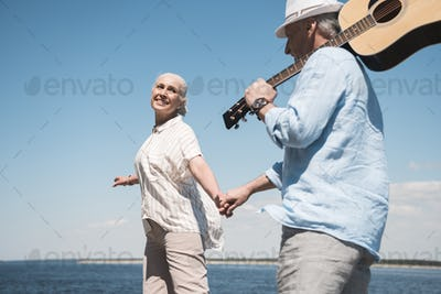 Happy senior couple with guitar holding hands and walking at quay