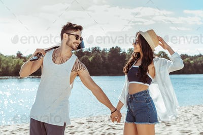 couple looking at each other during walk on beach on summer day