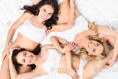 young sensual smiling women in white underwear looking at camera while lying on bed
