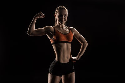 young smiling sportswoman flexing biceps and looking at camera