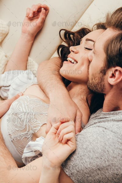 Close-up view of happy young couple hugging and kissing at home