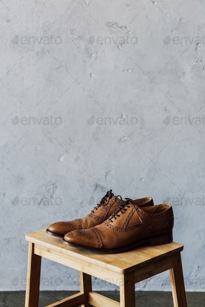 close up of brown leather oxford shoes on wooden stool