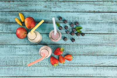 top view of milkshakes in glass bottles with berries and fruits on wooden tabletop
