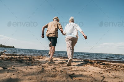 Back view of senior couple holding hands and running on sandy beach