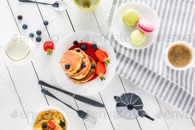 top view of pancakes with macarons and coffee with corn flakes on wooden tabletop