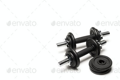 black iron dumbbells with weight plates isolated on white