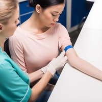 nurse preparing patient to do a blood analysis by fixing garrot on her arm