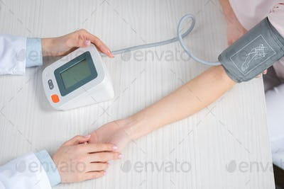Cropped shot of doctor measuring blood pressure to patient sitting at table