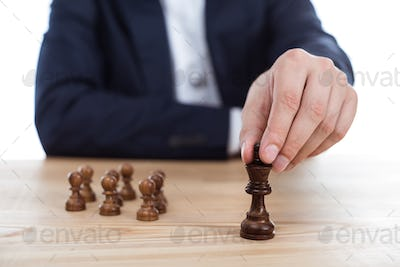cropped view of businessman holding chess figure in hand