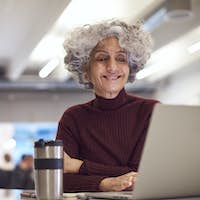 Mature Businesswoman With Travel Mug Working On Laptop In Kitchen Area Of Modern Office