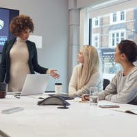 Pregnant  Businesswoman Leads Creative Meeting Of Women Collaborating Around Table In Modern Office