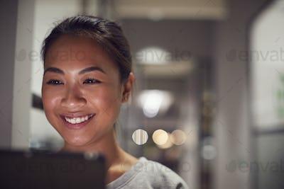 Evening Shot Of Businesswoman Standing In Corridor Of Modern Office Using Digital Tablet