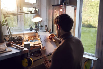 Male Jeweller Sketching Out Design For Ring In Studio