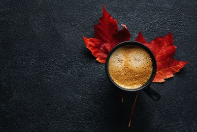 Coffee in cup with autumn leaves
