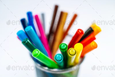 Colored pencils, pens and markers in a clerical case on white background