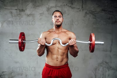 Sportive guy with muscular hands lifting barbell in background