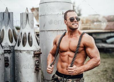 Smiling muscular tanned soldier guards old aircraft's ammunition