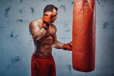 Strong confident man staying near bag with boxing gloves