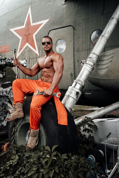 Strong bodybuilder and soviet helicopter in airport