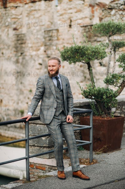 A man with a beard in a strict grey three-piece suit with a tie in the old town of Sirmione, a
