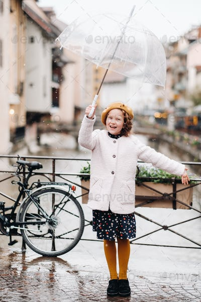 cheerful beautiful girl in a coat with a transparent umbrella in Annecy. France. The girl Cheerfully