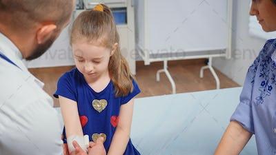Doctor bandaging child hand