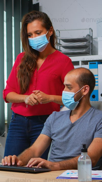 Workers talking wearing face masks