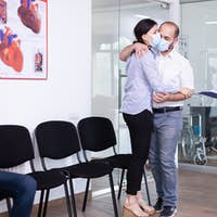 Disappointed couple sitting in hospital waiting area