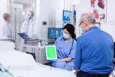 Patient looking at tablet with green screen