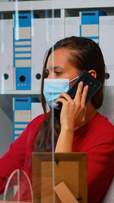 Woman talking on phone wearing mask