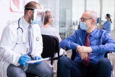 Invalid senior man talking with doctor