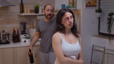 Alcoholic man screaming at beaten woman