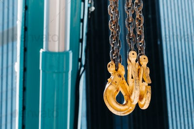 The hooks of the mobile crane near the glass of high buildings.Lots of hooks hanging from chains
