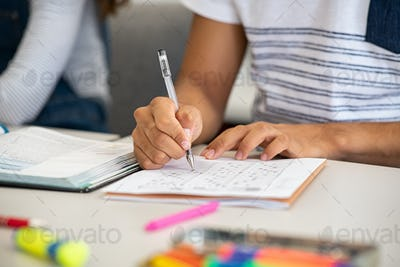 High school student filling out test answers with pen