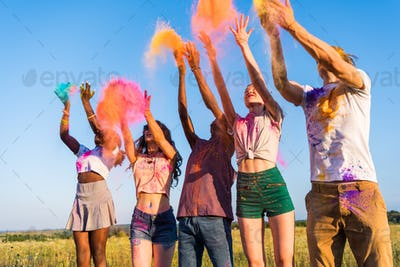 happy young multiethnic friends throwing colorful powder at holi festival