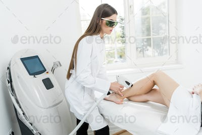young hair removal therapist in coat with laser epilator