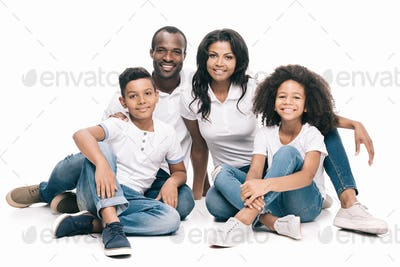 beautiful happy african american family sitting together and smiling at camera isolated on white