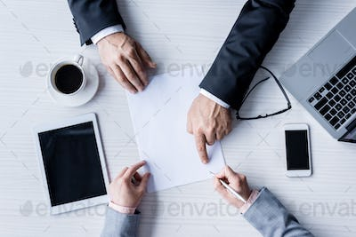 top view of business partners signing contract during meeting