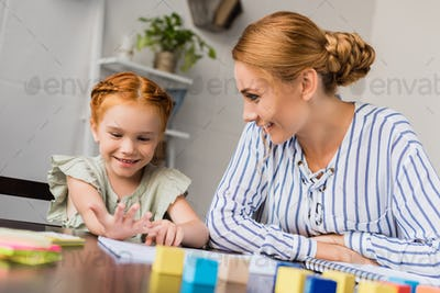 young mother and happy smiling daughter learning math at home