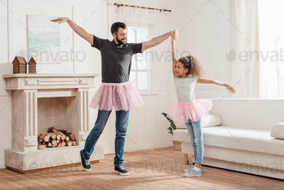 multicultural Father and daughter in pink tutu tulle skirts dancing together at home