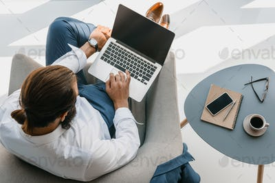 top view of businessman using laptop while sitting in armchair